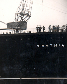 A big ship with the name Scythia pulls into port.
