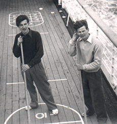 Two men standing are playing shuffleboard while on the ship's deck.