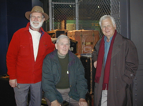 Three older men wearing jackets stand together.