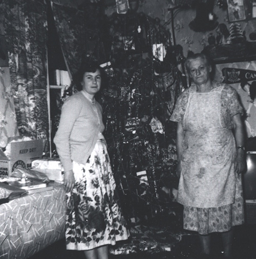 Black and white photograph of two women, one older wearing an apron, standing next to a decorated Christmas tree