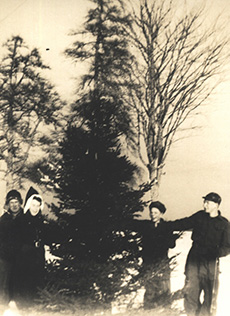 A black and white photograph of two men, and woman and a boy, outside wearing coats and hats, laughing next to a very tall evergreen tree