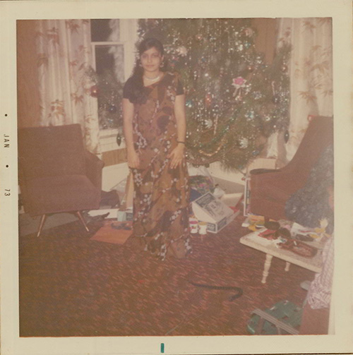 A faded colour photograph of a woman dressed in a sari standing in front of a decorated Christmas tree, opened boxes and packages surround the base of the tree