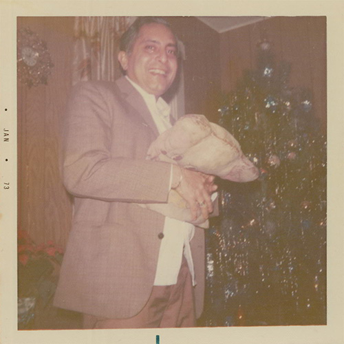 A faded colour photograph of a well-dressed man smiling next to a decorated Christmas tree, holding a full burlap sack of unknown contents