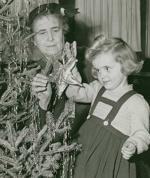 A black and white photograph of a young girl hanging an ornament on a Christmas tree, an older woman helps her.