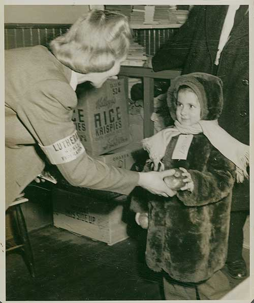 A black and white photograph of a young girl in a winter coat taking an apple being offered to her by a woman.