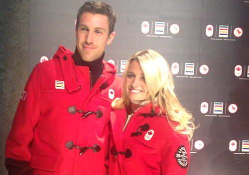 Young couple wearing dark red Olympic clothes stand together.