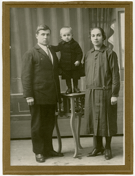 Archival black and white photo of a couple with their little son standing on a table.