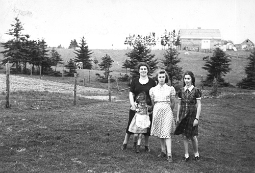 Three girls standing on the grass with a young woman.