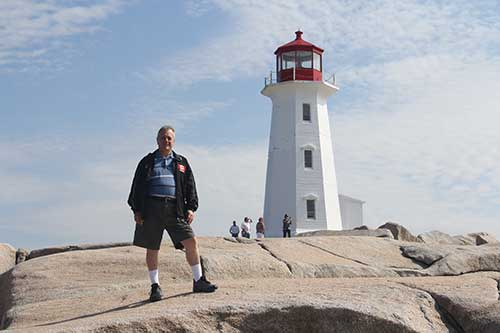 Man standing on rocks close to the Peggy's Cove lighthouse.