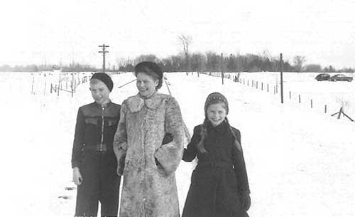 Two children link arms with their mother as they walk down a snow-covered road.