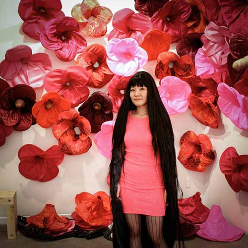 Beautiful big flowers made of fabric cover a wall. A woman with very long dark hair stands in front of the wall.