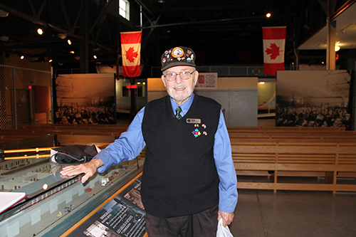 Older gentleman wearing baseball cap, standing next to exhibit