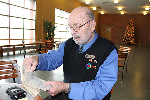 Older gentleman looking through pages of address book