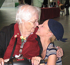 Young woman bending down to look at a woman in a wheelchair, she smiles affectionately at her.