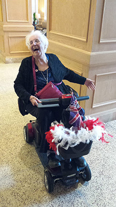 Elderly woman laughing as she sits in a wheelchair with lots of Union Jack flags attached.