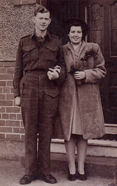 Young man in military uniform stands next to his new bride.