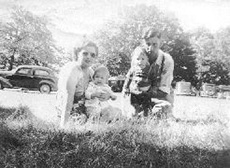 Old faded photograph of a couple and their kids sitting on the grass.