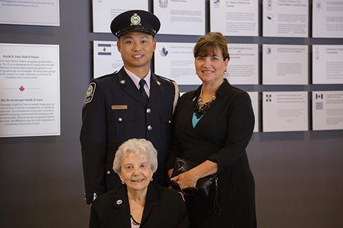 Un policier en uniforme parle à deux femmes à côté du mur d'honneur de Sobey.