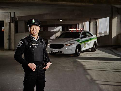 Un policier en uniforme se tient à côté de sa voiture de police et pose pour la caméra.<br />
