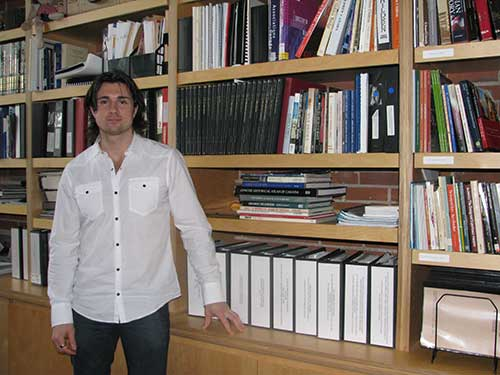 A young man is standing in front of book shelf.