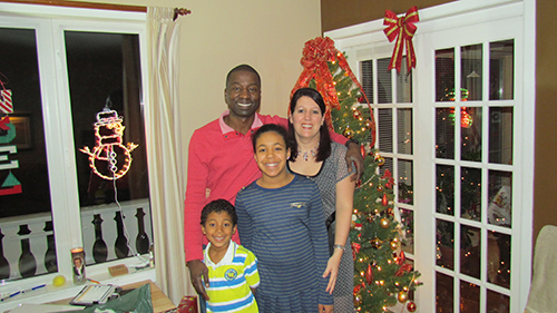 A couple with their children standing beside the Christmas tree.