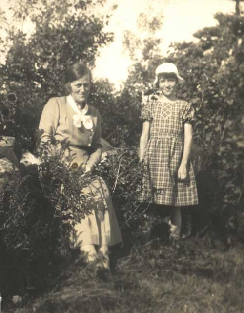 A young woman and little girl sit in a garden.
