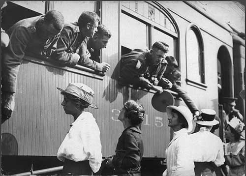 Side view of a train, men in First World War uniform lean out the windows to say goodbye to women on the platform