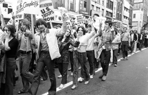 An archived black and white photo of young people carrying signs, marching in protest.